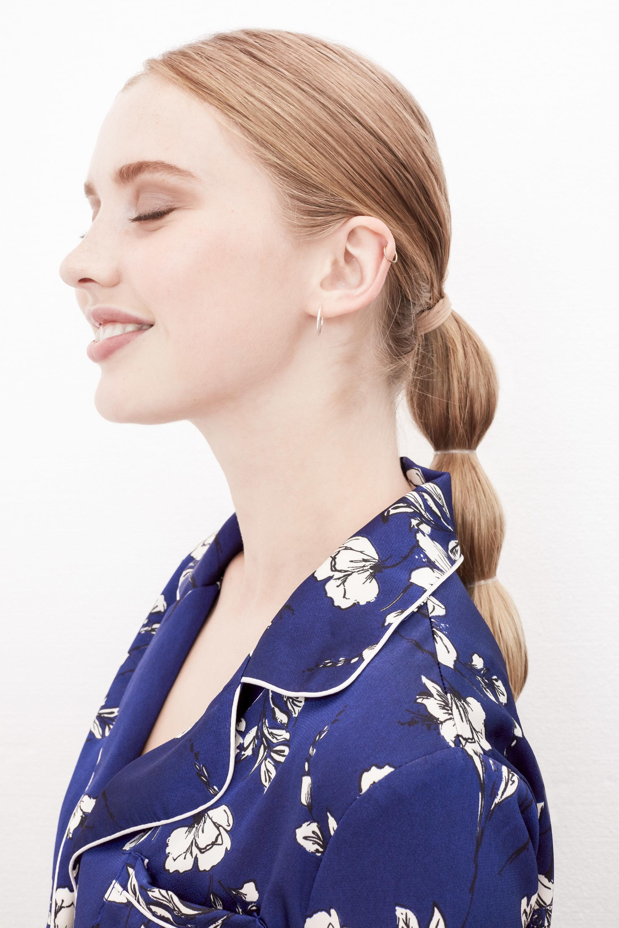 Easy braids for long hair: Side profile of a woman with long dark honey blonde hair in a bubble ponytail hairstyle, wearing a blue floral top