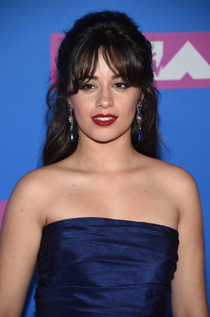 Close up shot of Camila Cabello with long chocolate brown hair styled into a half-up, half-down updo, complete with curtain bangs on the VMA red carpet.