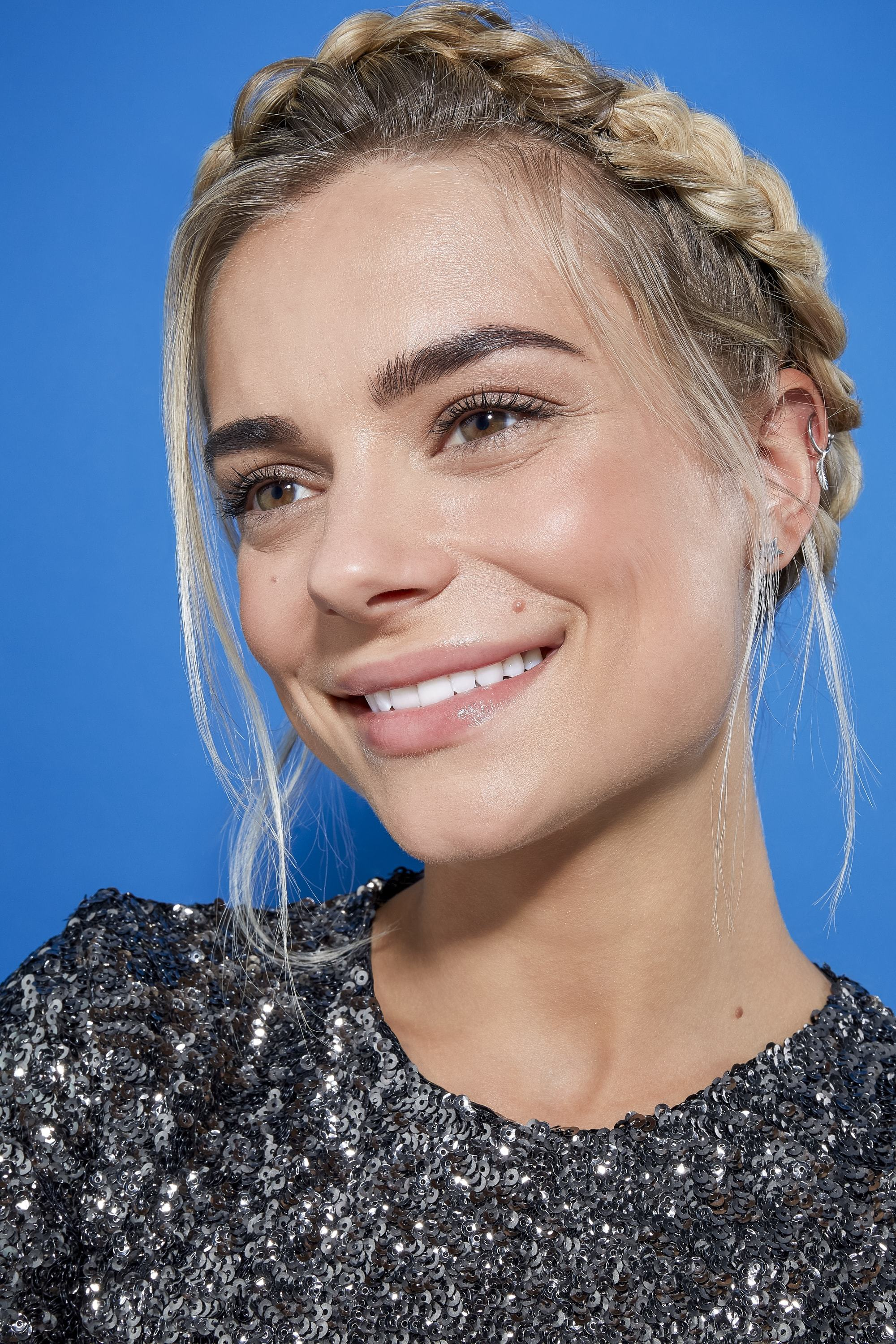 Easy braids for long hair: Blonde woman with her hair in a crown braid, wearing a sequin top