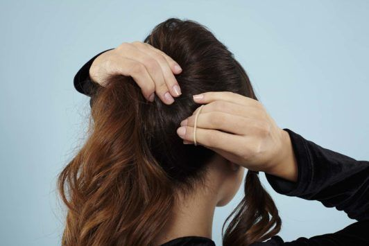 Curly ponytail tutorial: Back view of a brunette model creating her ponytail