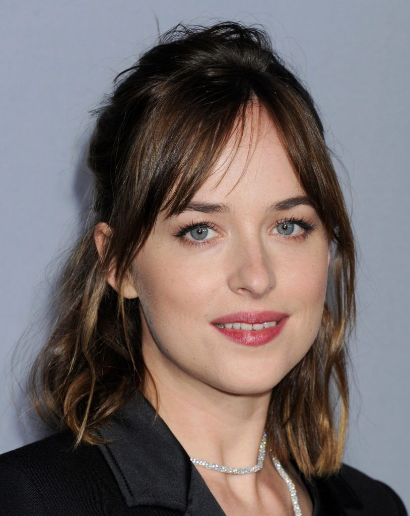 close up shot of dakota johnson with split bangs and half up style on the instyle awards red carpet
