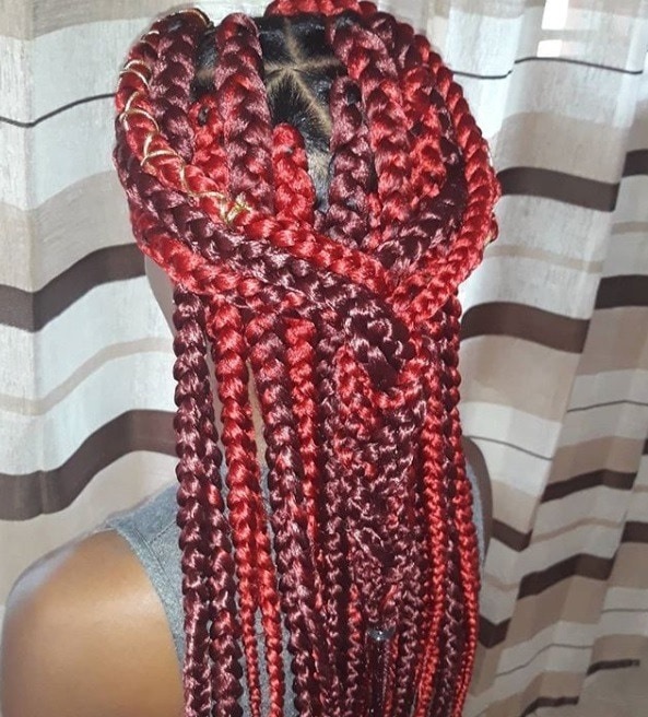Dookie braids: Close up shot of red box braids styled into a half-up, half-down braid.