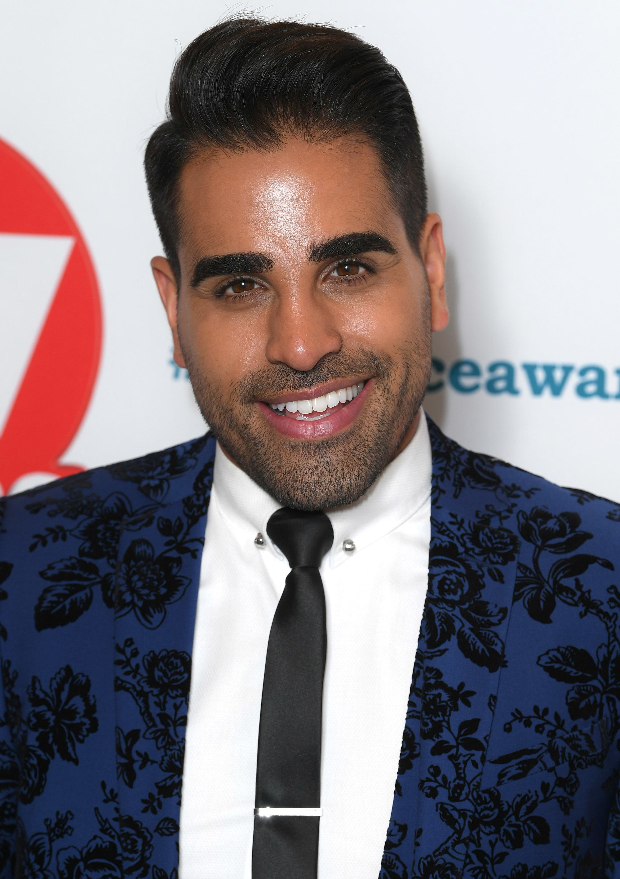 TV Choice Awards: Close up shot of Dr.Ranj Singh with medium dark brown hair styled into a slick combover, wearing dark blue and black suit on the red carpet