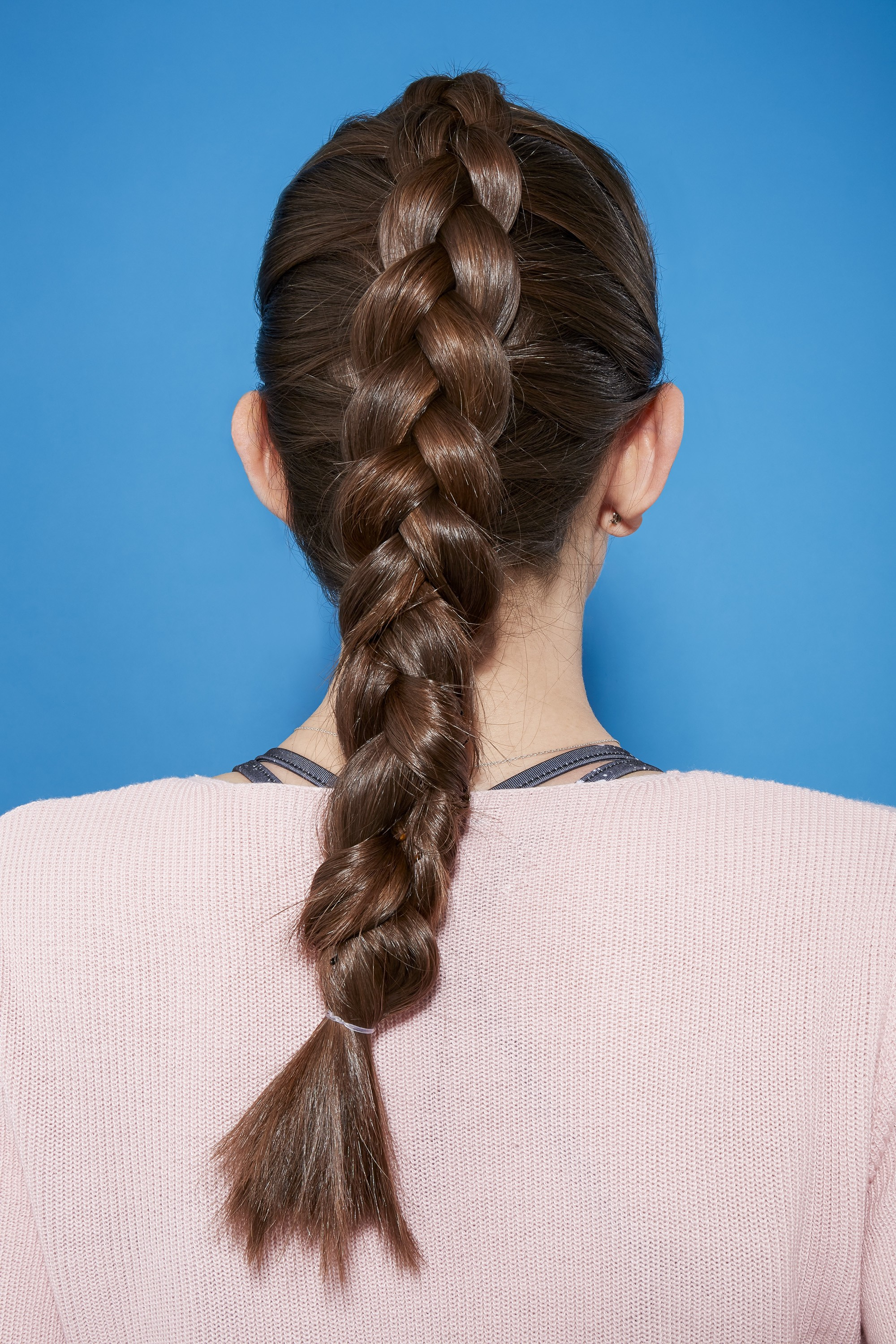 Easy braids for long hair: Back view of a brunette with long hair in a Dutch braid hairstyle, wearing a sports bra and pink gym top against a blue background