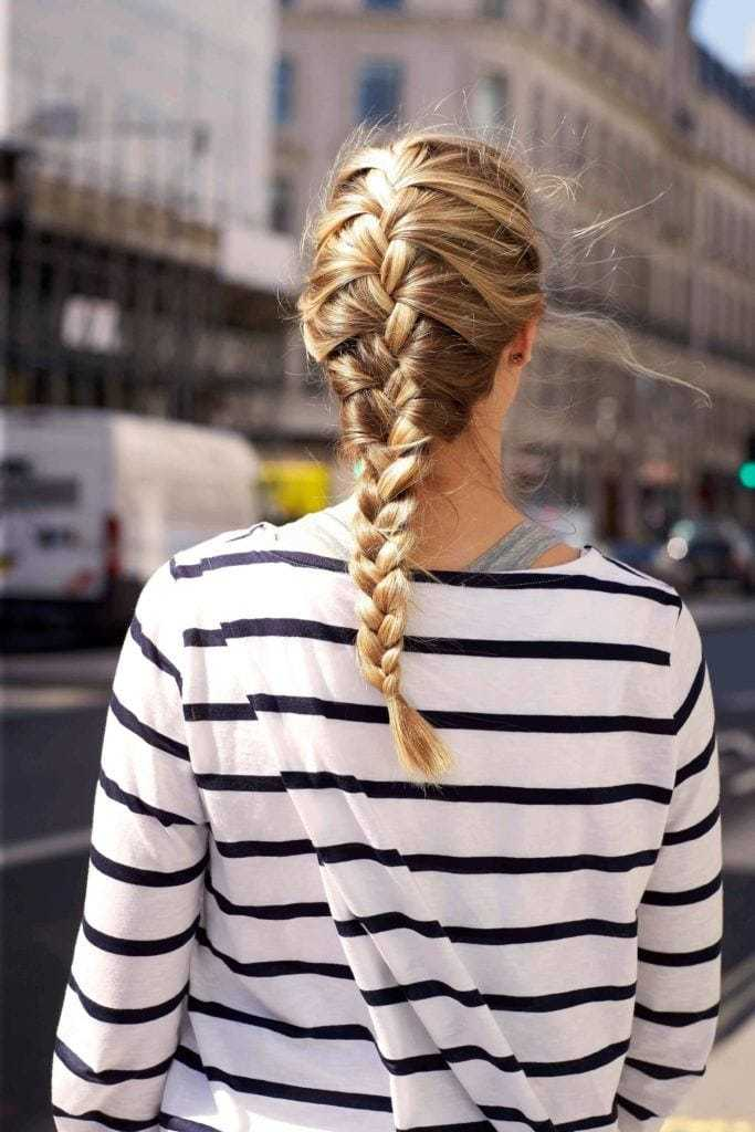 Easy braids for long hair: Back view of a blonde woman with a French braid hairstyle, wearing a stripy breton top