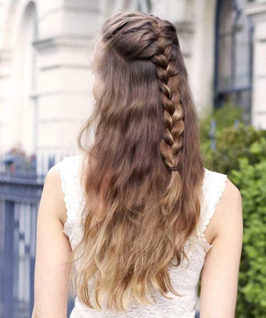 Easy braids for long hair: Back view of a woman with brunette ombre long wavy hair in a half-up braided hairstyle