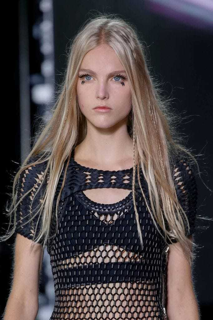 Easy braids for long hair: Blonde runway model with long straight hair with skinny accent braids, wearing a black mesh top