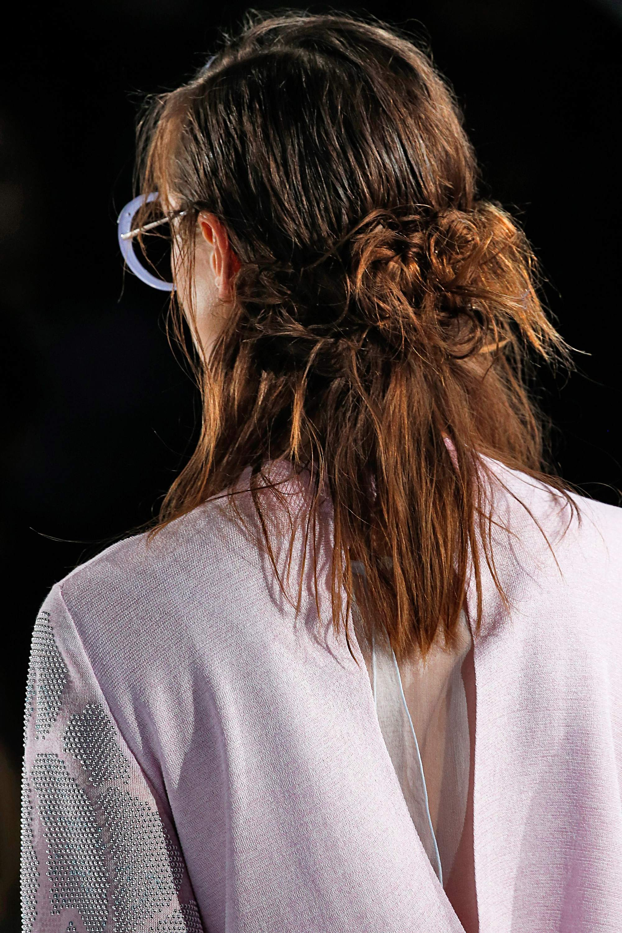 back view runway shot of a brunette emporio armani model with her hair in a half up buns style