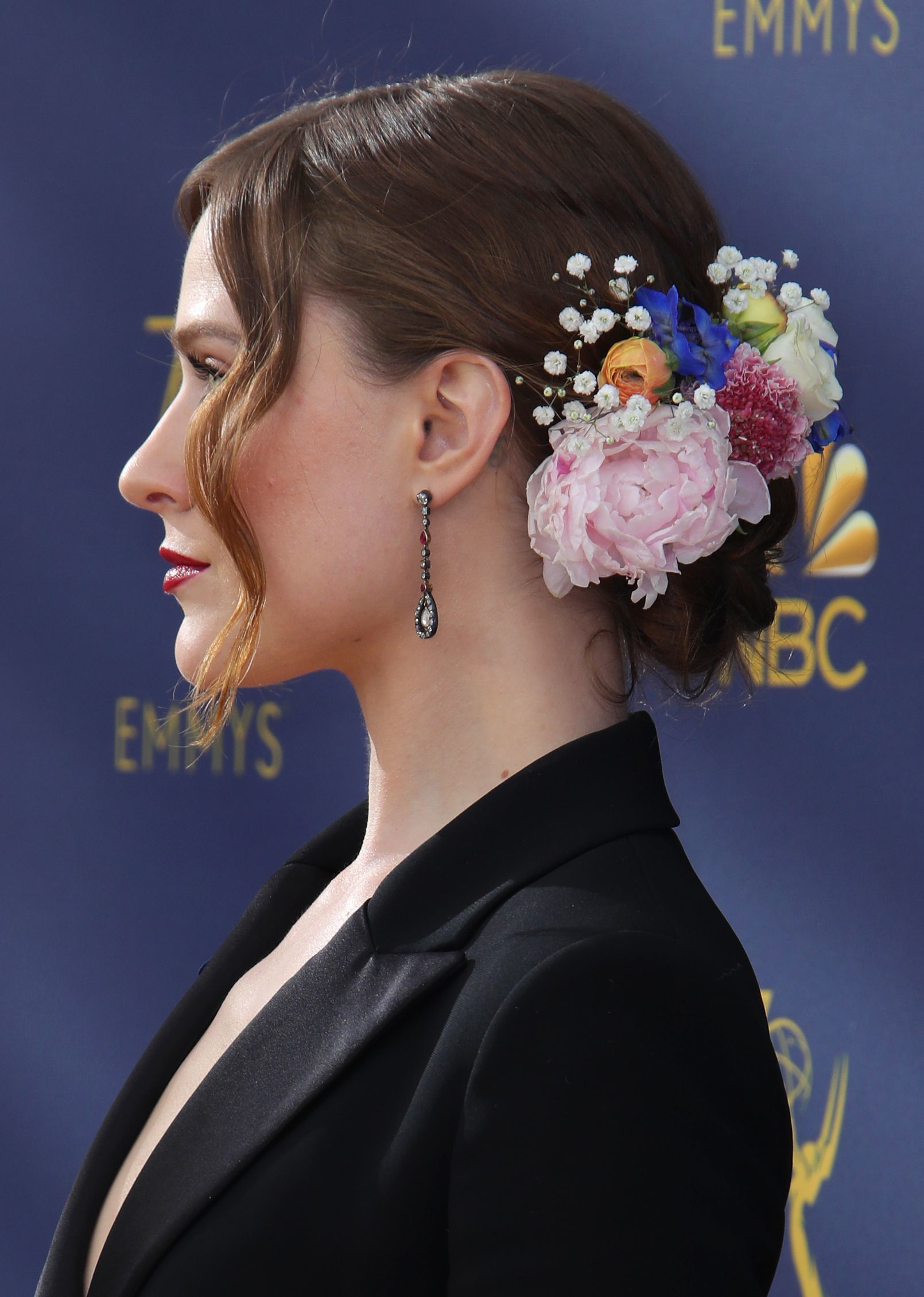 Emmy Awards 2018: Close up shot of Evan Rachel Wood with a romantic medium brown low bun decorated with flowers, wearing a black blaxer and drop earrings on the red carpet