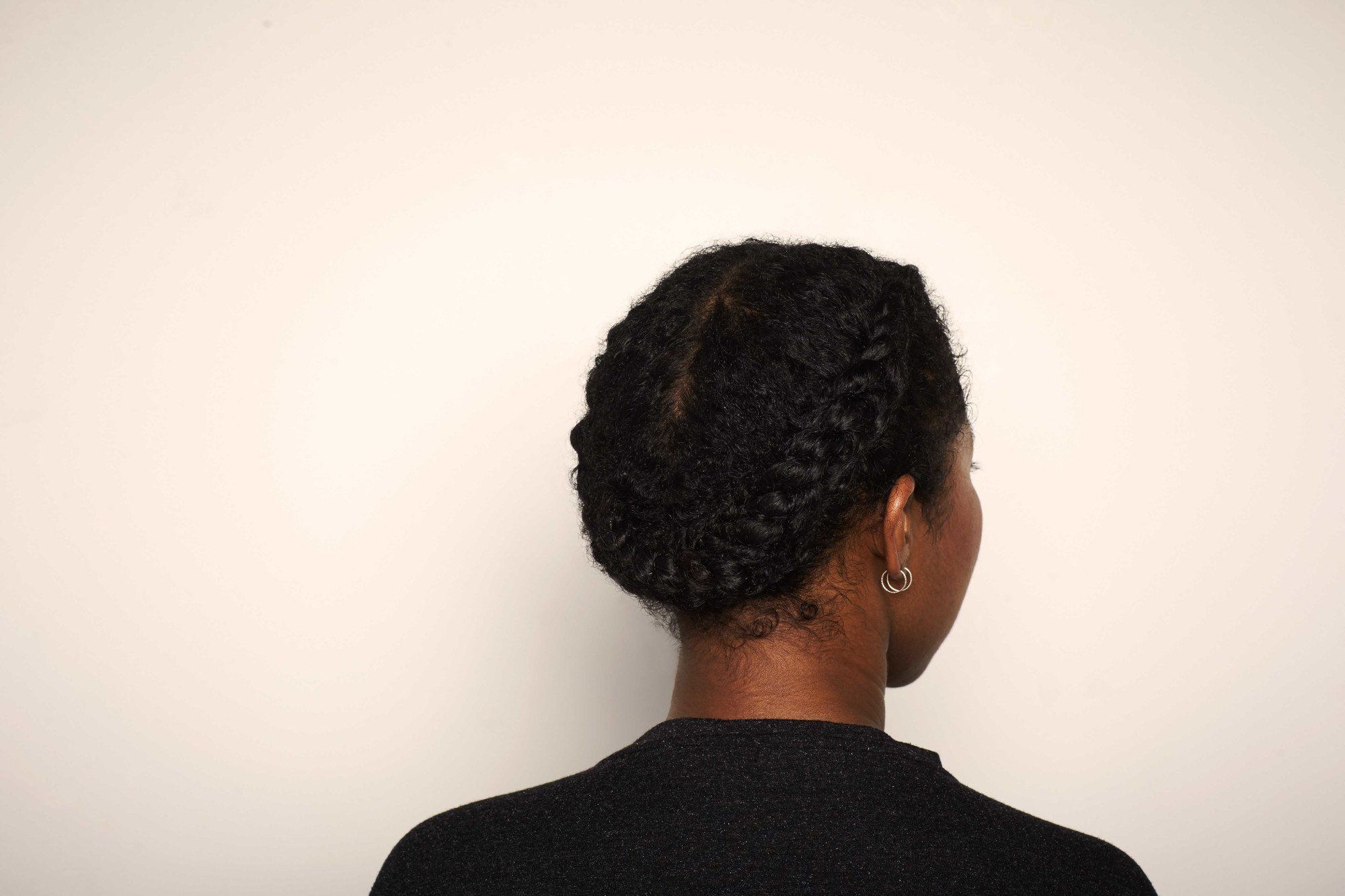 back shot of a woman with her afro hair in a flat twist halo braid style
