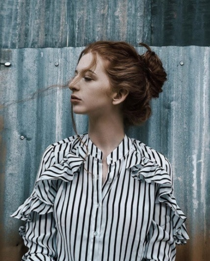 side profile shot of a redhead woman with her hair in a bun