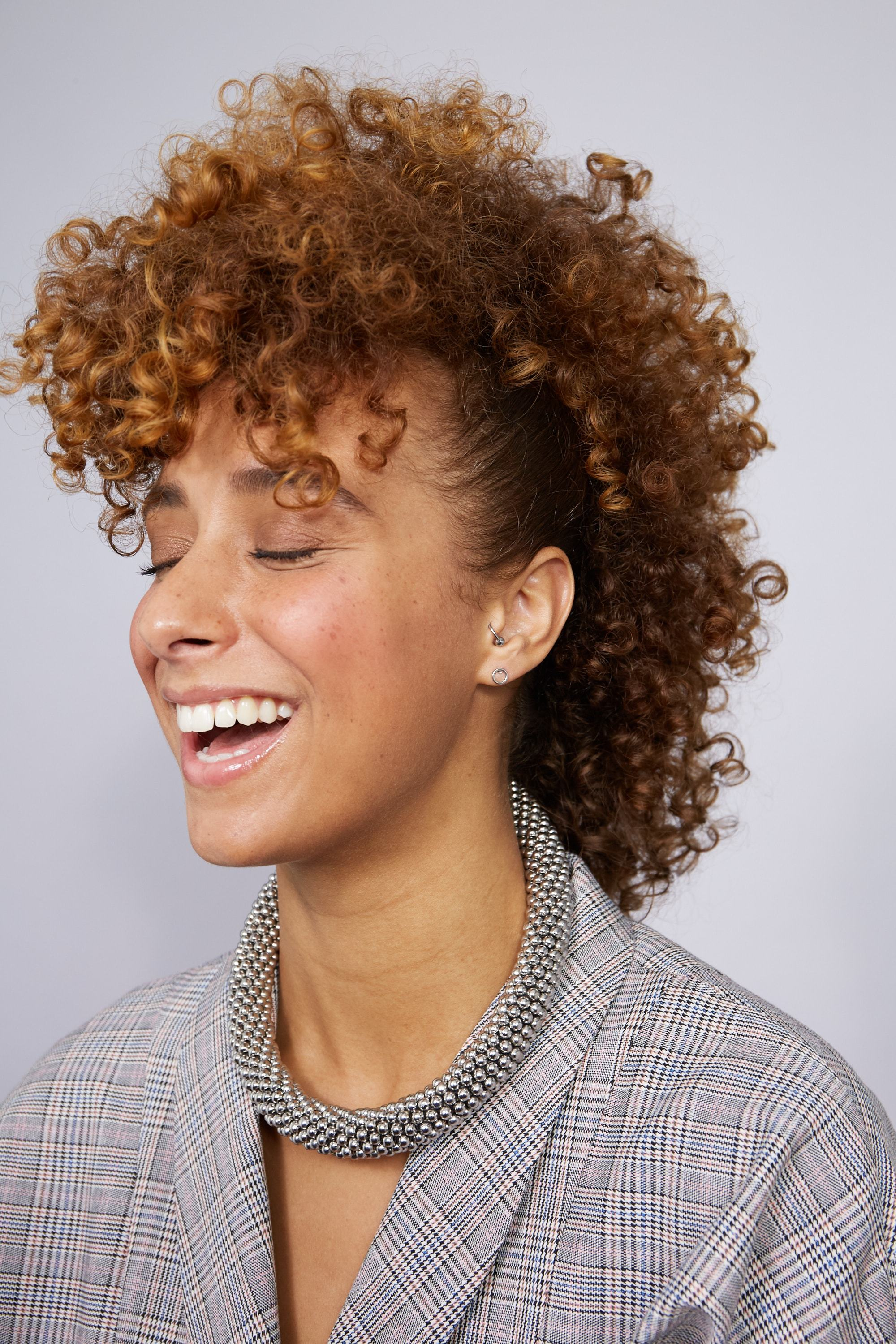 Party hair tips: Woman with natural caramel brown medium afro curls hair styled into frohawk, wearing a checked blazer and a silver necklace