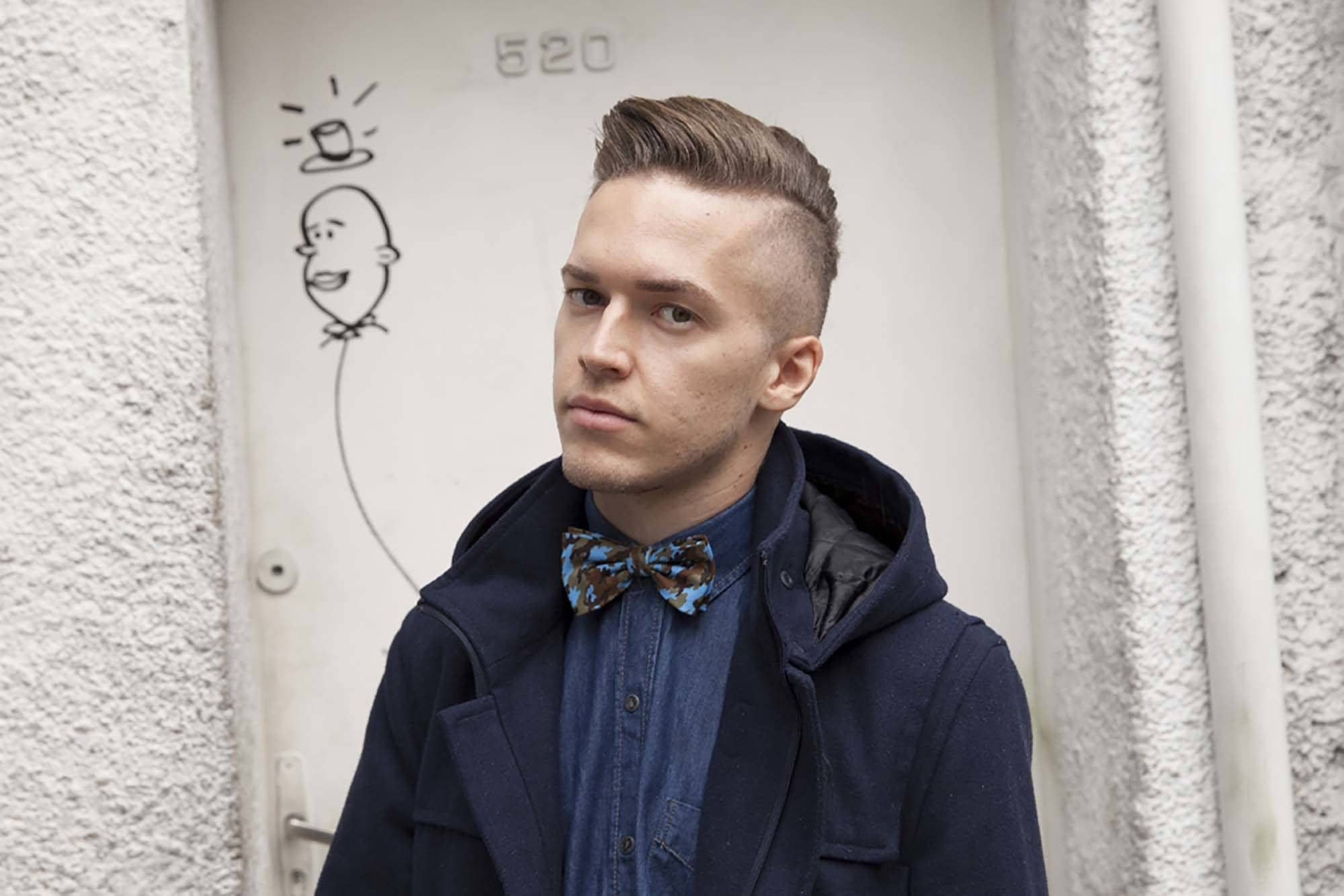 what is a taper fade guide: street style shot of man with bald taper cut wearing bow tie and jacket