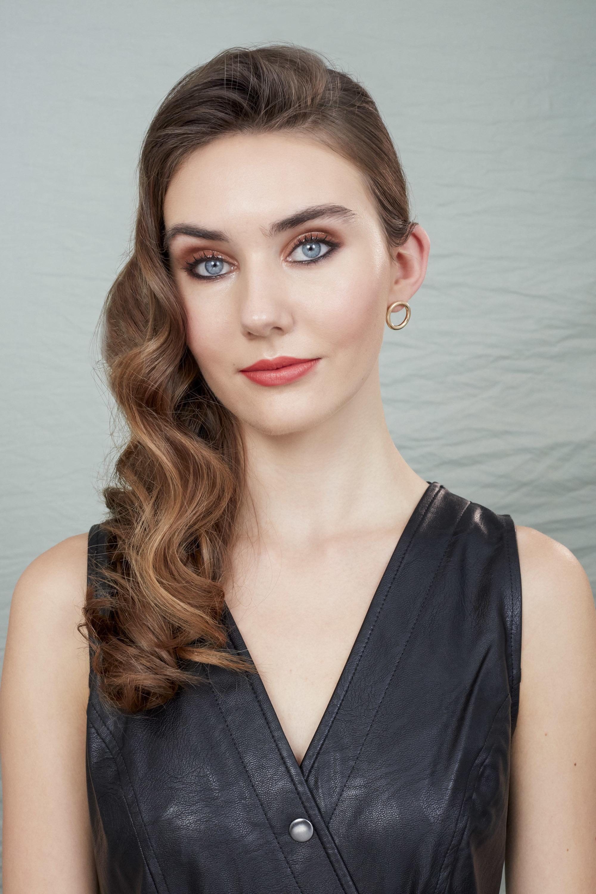 Party hair tips: Woman with long, wavy chestnut brown hair styled into Hollywood curls wearing black leather dress and posing in a studio setting