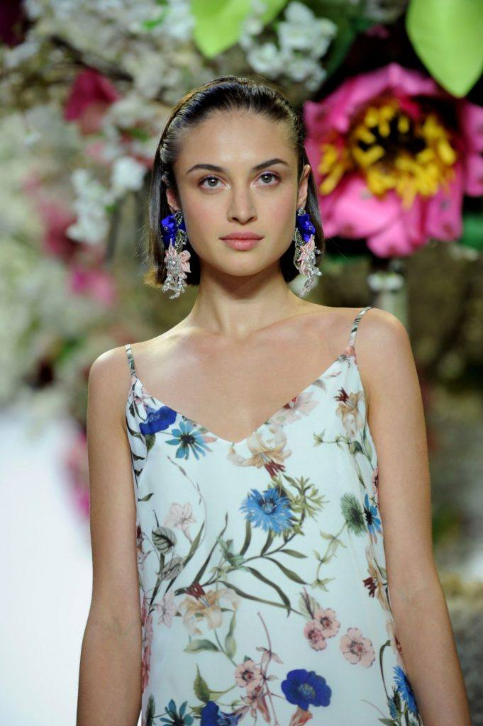 NYFW SS19: Close up shot of a model on the Badgley Mischka runway with short sleek bob styled slicked back, wearing floral outfit and walking down the runway