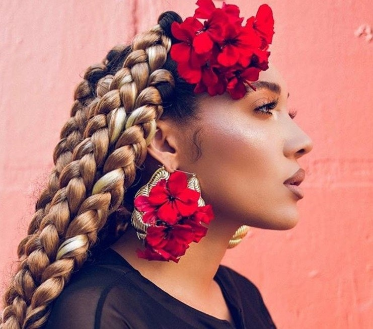 Side shot of woman with golden dookie braids with flowers in them.