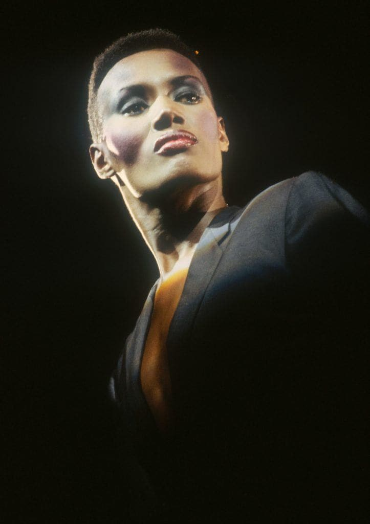shot of grace jones with iconic hightop hairstyle wearing black on stage
