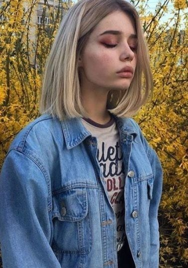 photo of a woman in a field wearing a denim jacket with a grungey 90s bob hairstyle