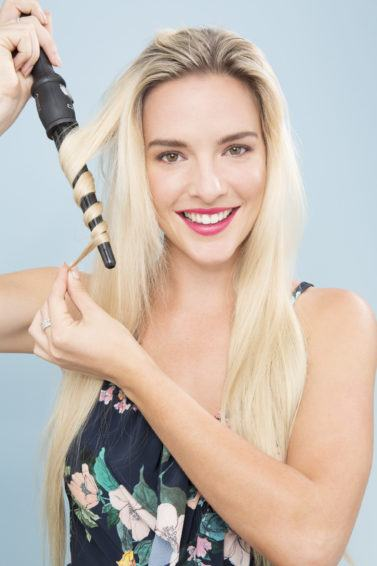 blonde model with long hair using a curling wand to curl her hair