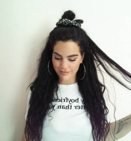 woman with dark brunette long hair in a half up bun tied with a scrunchie