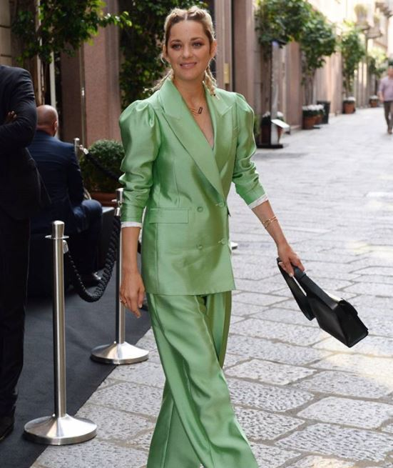 Marion Cotillard blonde hair in two french braids wearing green suit at Milan Fashion Week