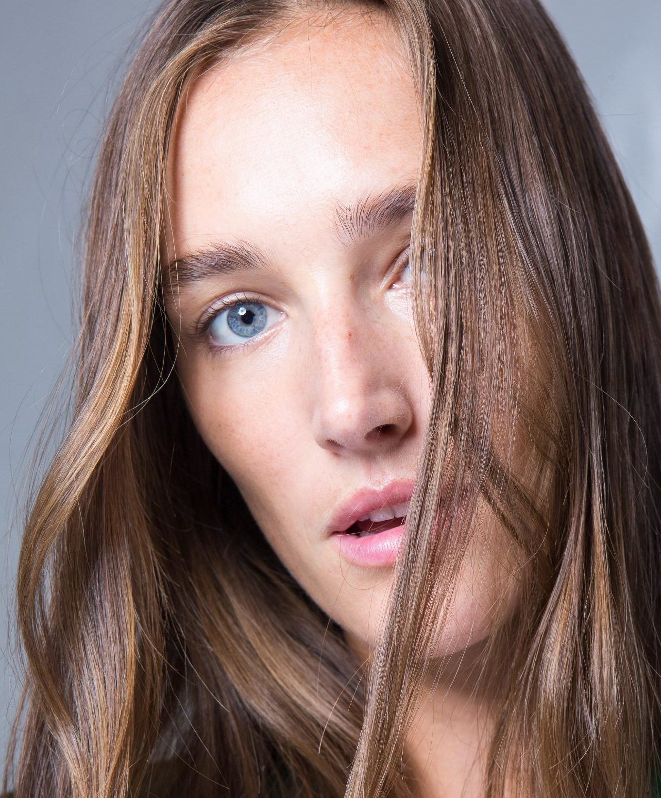 Anti-frizz spray: Model backstage at SS19 Isabel Marant show with wavy brown hair.