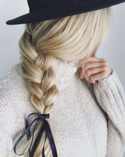side view of medium length blonde hair with side braid and ribbon at the bottom