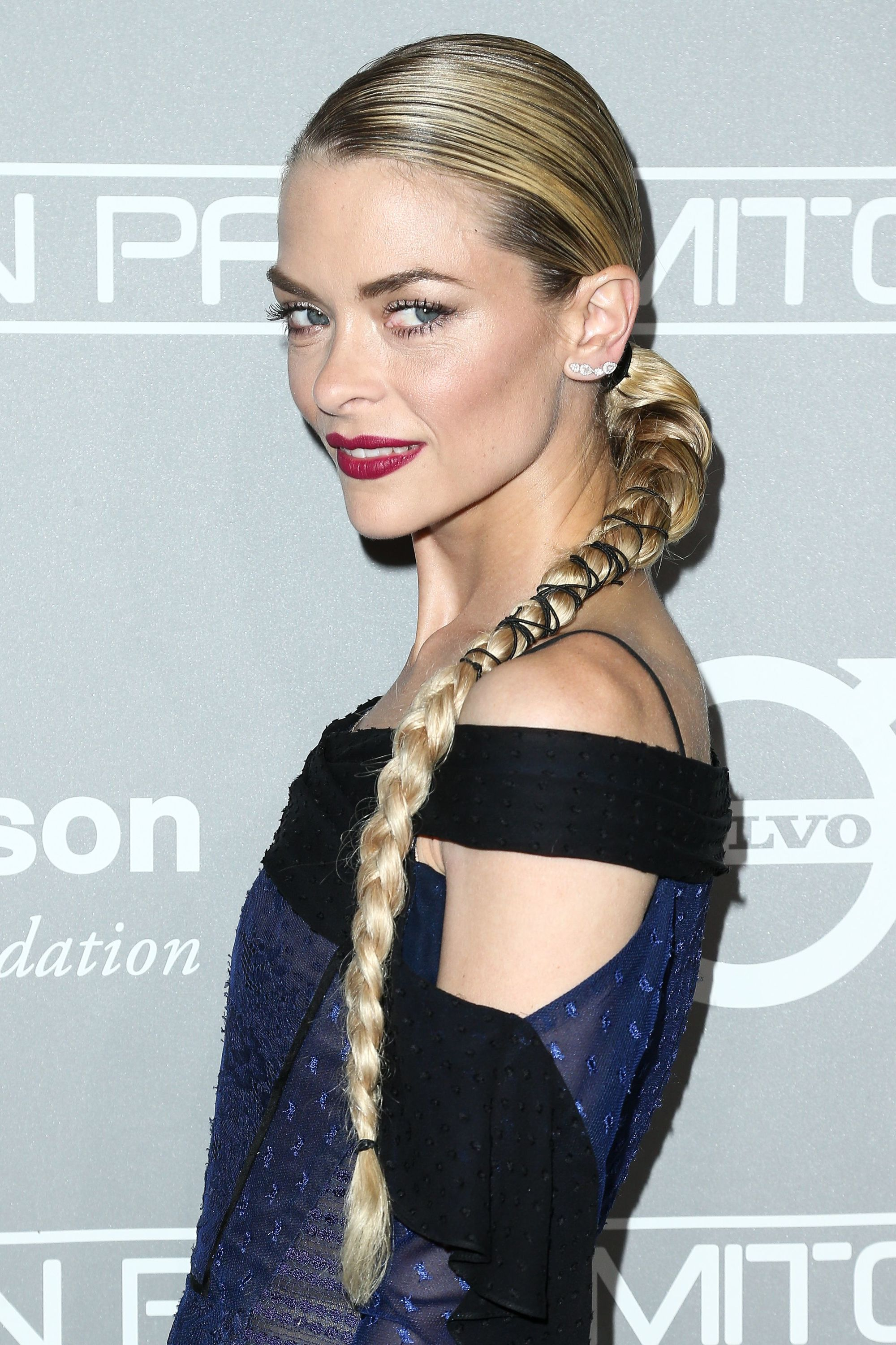shot of jamie king with party braids that have been wrapped with ribbon, wearing black on the red carpet