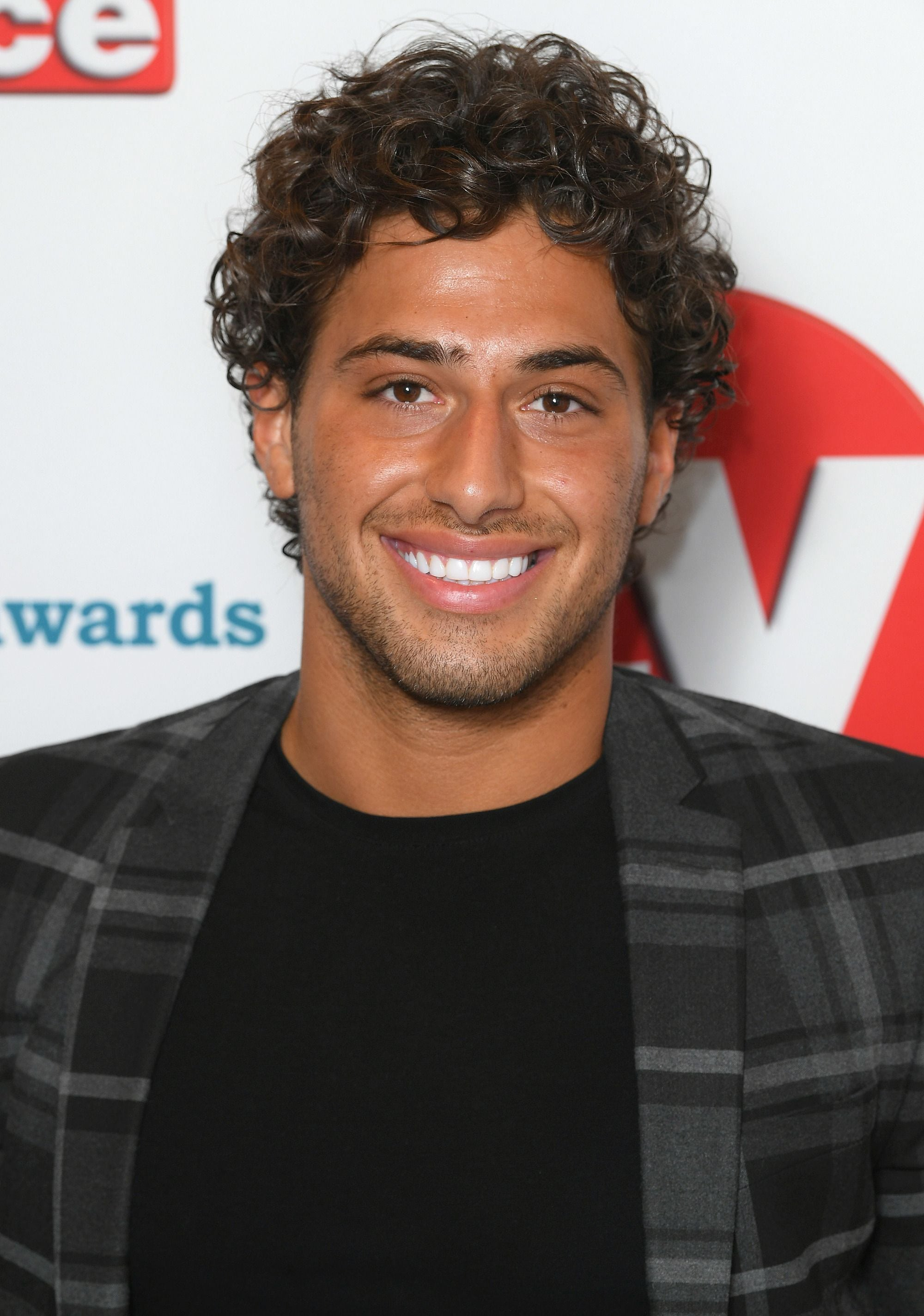 TV Choice Awards: Close up shot of Kem Cetinay with medium chocolate brown curly crop, wearing check blazer on the red carpet