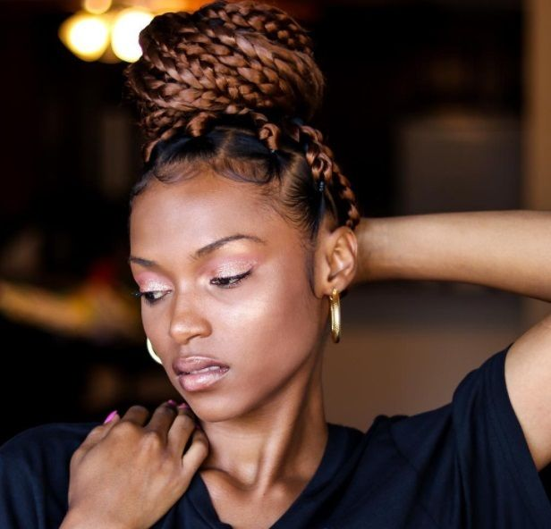 Shot of woman with dookie braids styled into a high bun updo