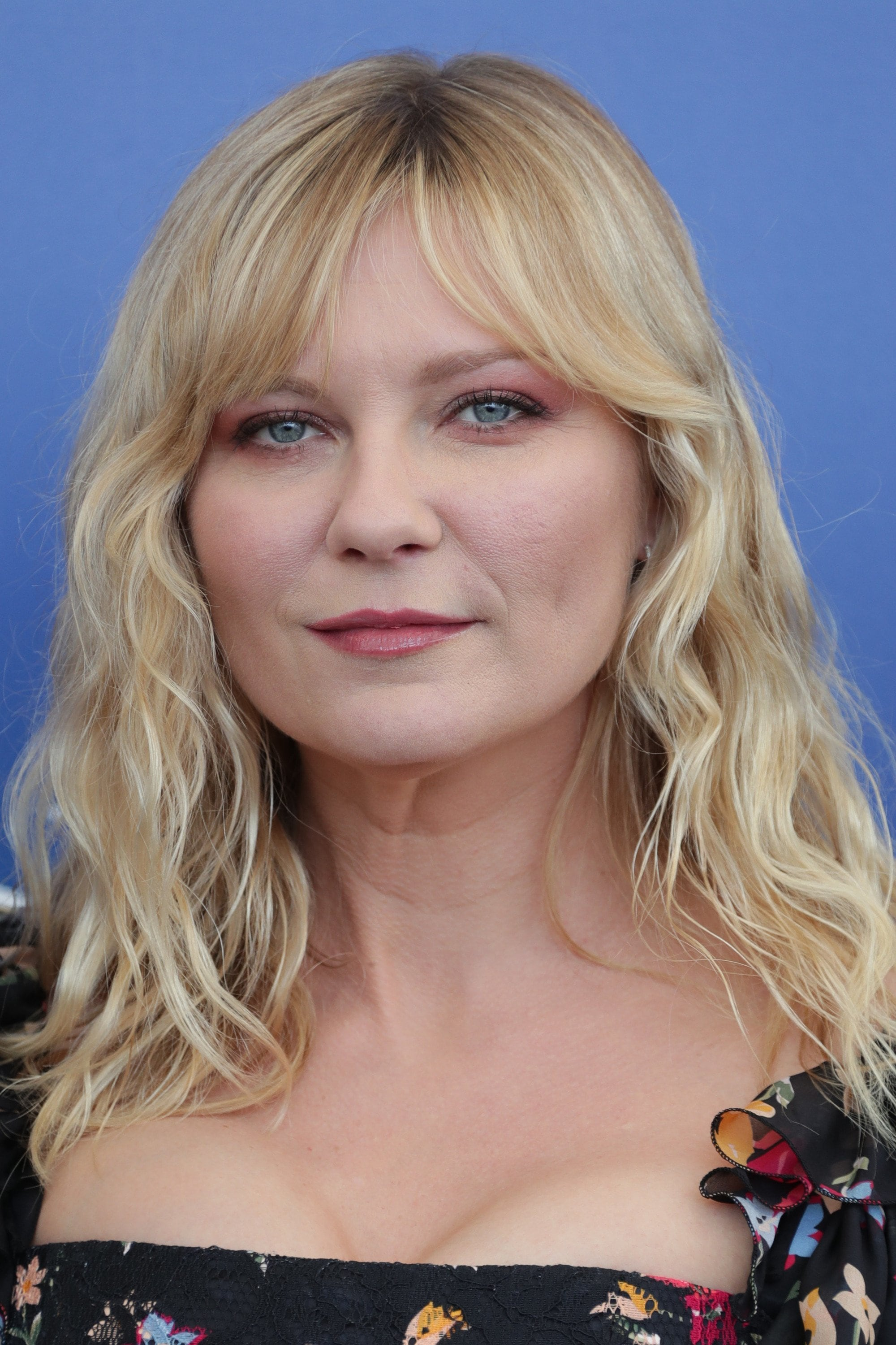 actress kirsten dunst with wavy blonde hair and parted bangs