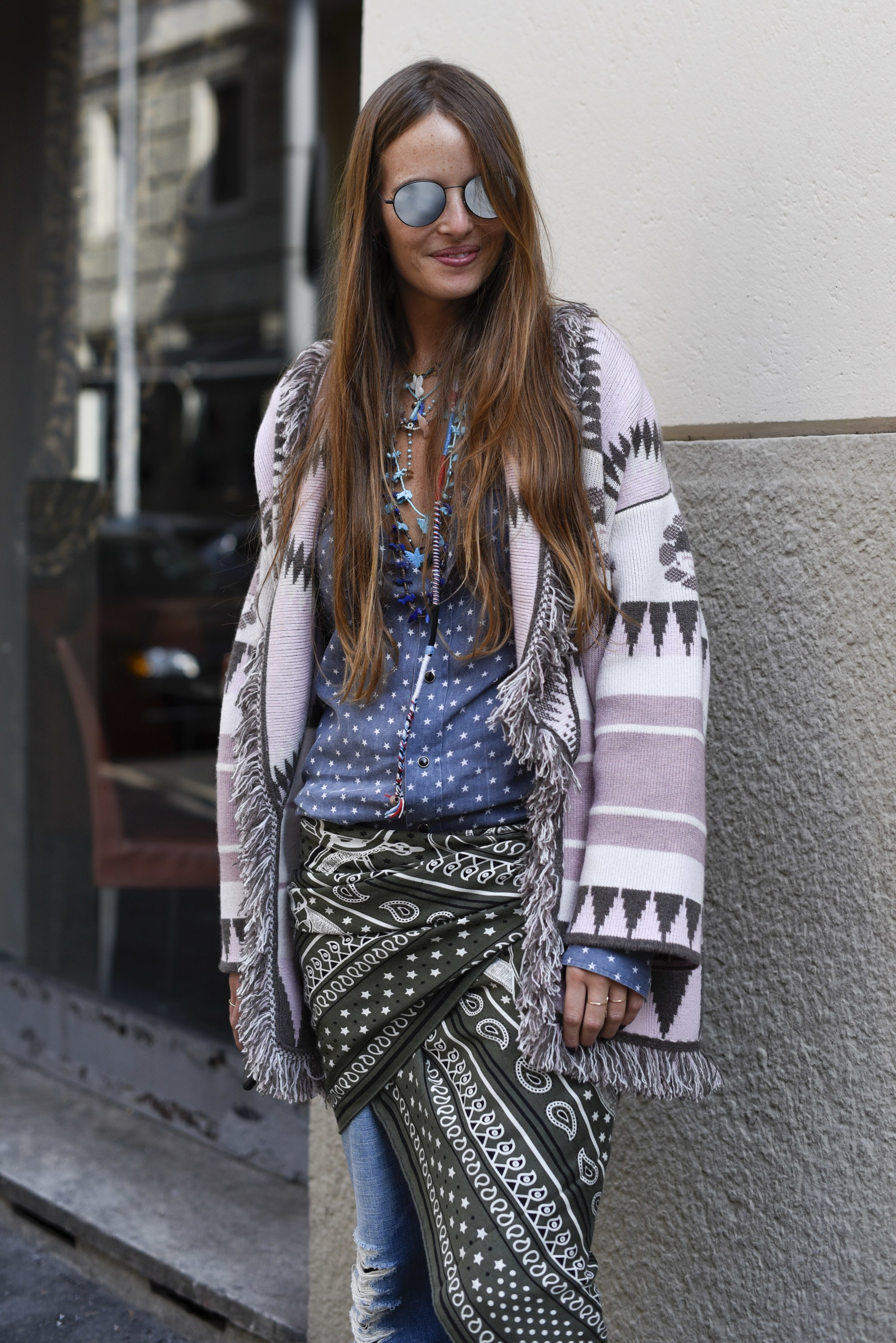 street style shot of a woman with long brunette hair wearing mirrored sunglasses and a bohemian outfit