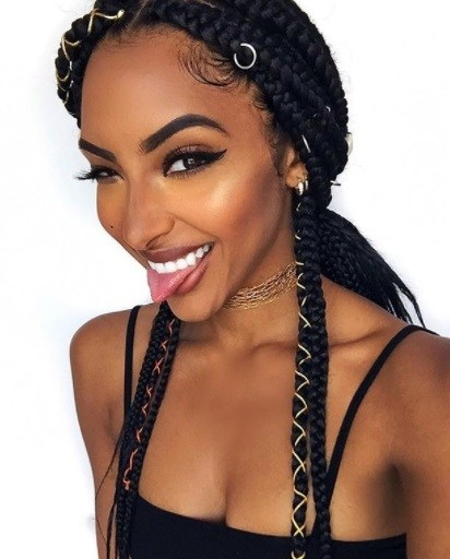 close up shot of woman with low braids in a ponytail, that are accessorised smiling