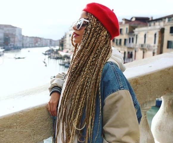 Dookie braids: Close up shot of a woman with long blonde braids with a red beret hairstyle standing on a bridge.