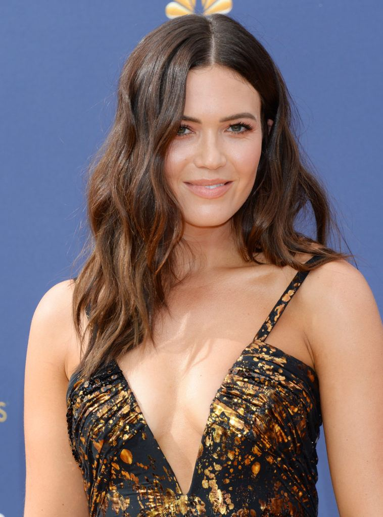 Emmy Awards 2018: Close up shot of Mandy Moore with chocolate brown medium beachy waves, wearing a gold and black dress on the red carpet