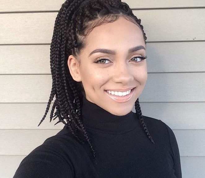 medium box braids styles: shot of woman with medium box braids smiling with her hair styled into a half up ponytail