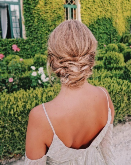 back view of a woman with blonde hair in a messy braided updo