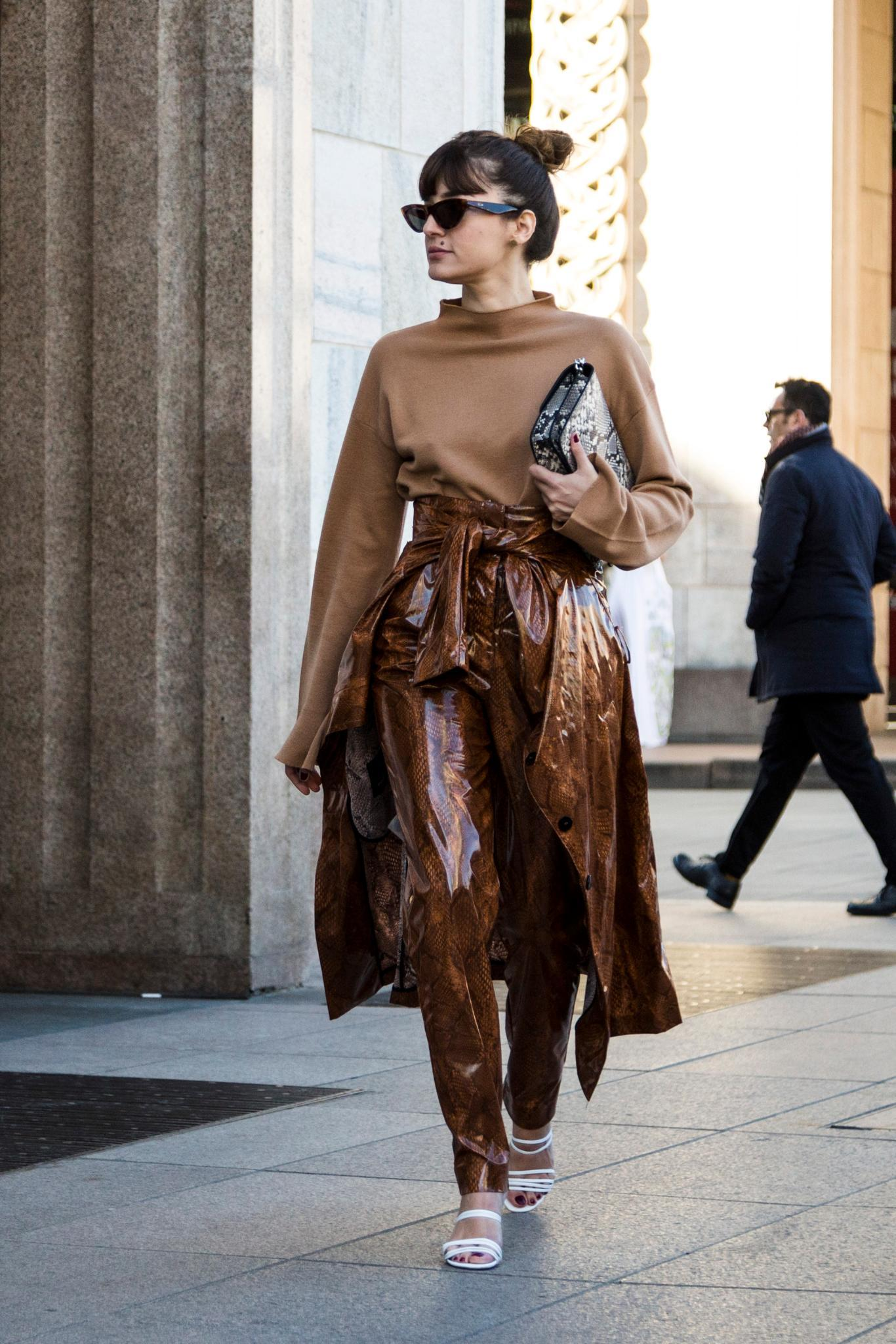 Milan Fashion Week Street Style: Woman with dark brown hair in high messy bun with full fringe bangs wearing all brown outfit holding a clutch bag.