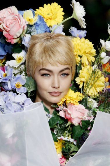 close up shot of gigi on the runway with pixie cut wig and a floral costume