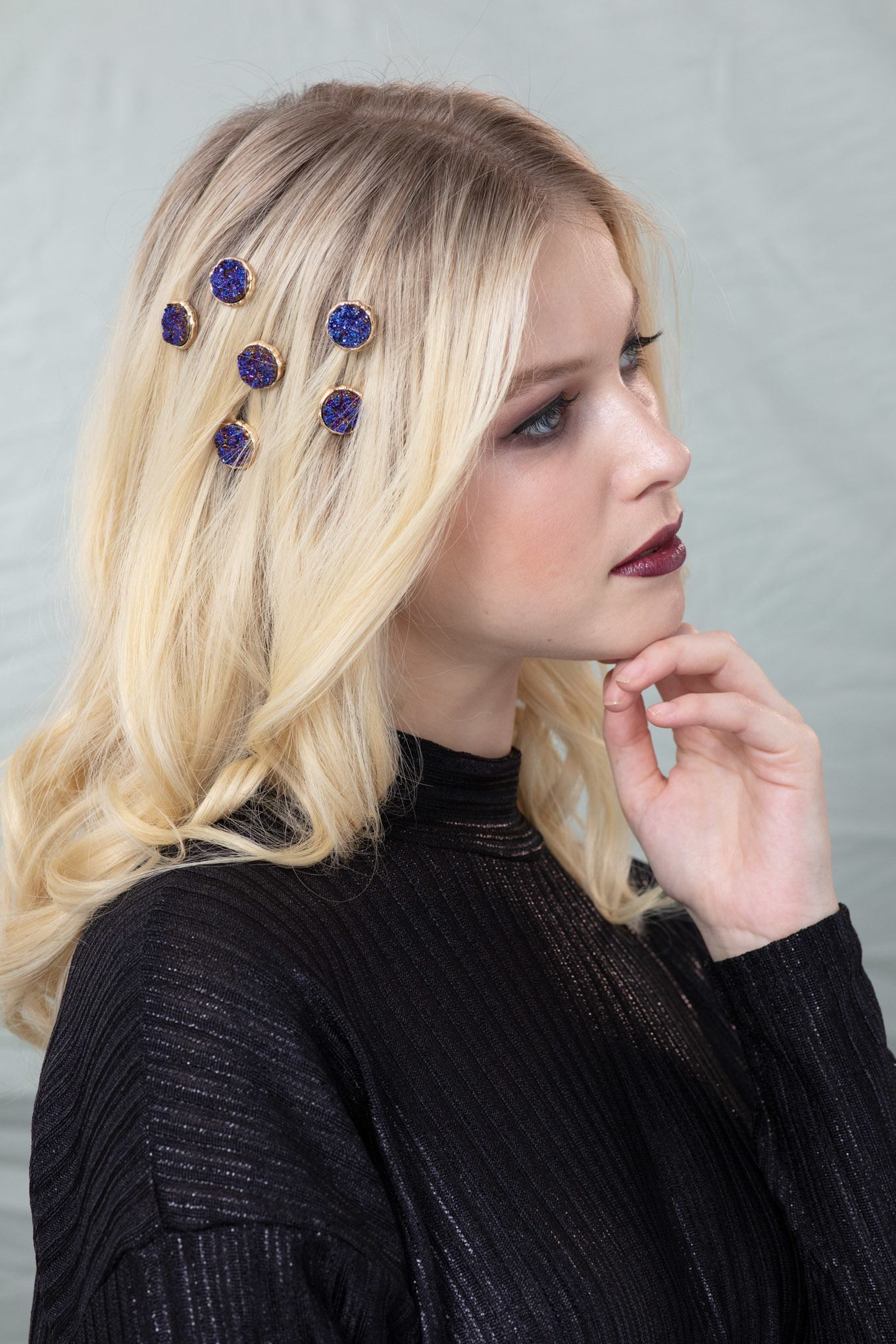 Woman with golden blonde hair styled into loose waves and decorated with Aaron Carlo volcanic hair accessories, wearing a blue top with dark makeup in a studio setting