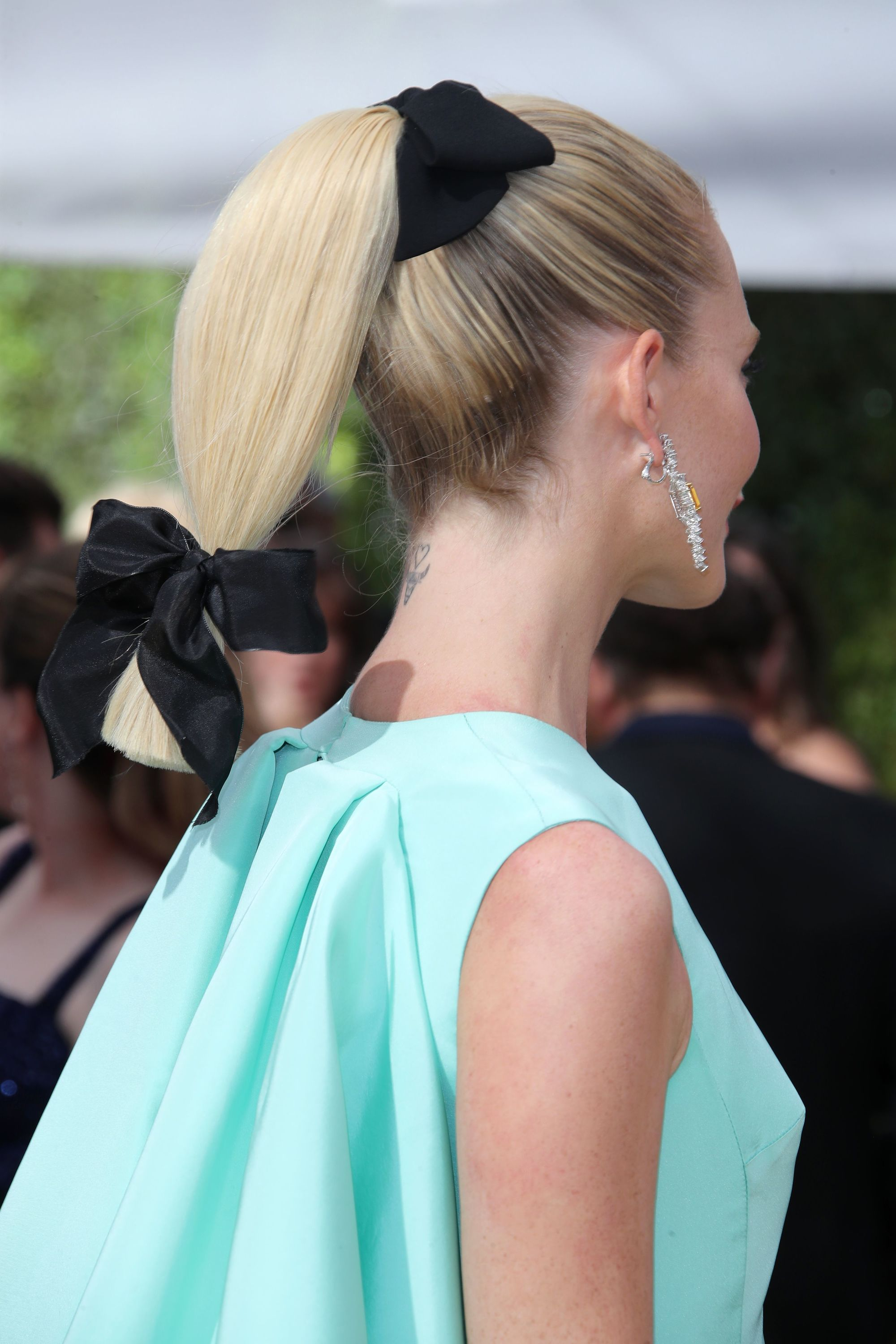 Emmy Awards 2018: Close up back shot of Poppy Delevingne with medium platinum blonde hair styled into a low ponytail with bow hair accessories, wearing a teal dress and drop earrings on the red carpet