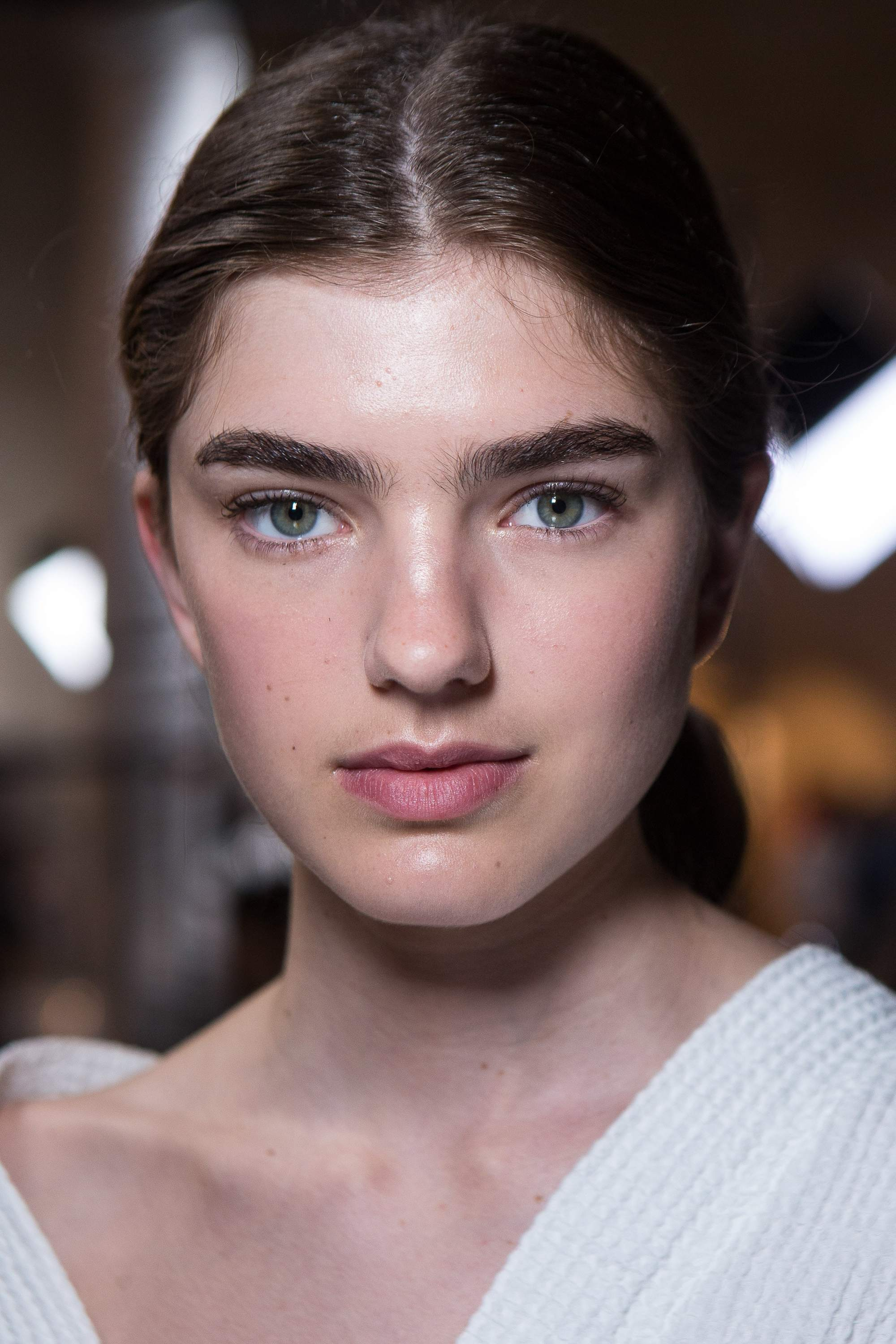brunette model backstage at a fashion show with bushy brows