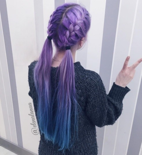 back shot of a woman with long purple and blue ombre hair in braids