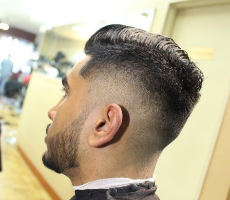 side shot of a man with quiff hair and a bald taper fade
