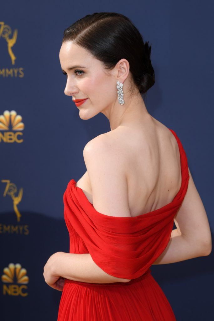 Emmy Awards 2018: Close up side shot of Rachel Brosnahan with medium dark brown hair styled into an elegant low bun, wearing a red off-the-shoulder gown with silver earrings on the red carpet