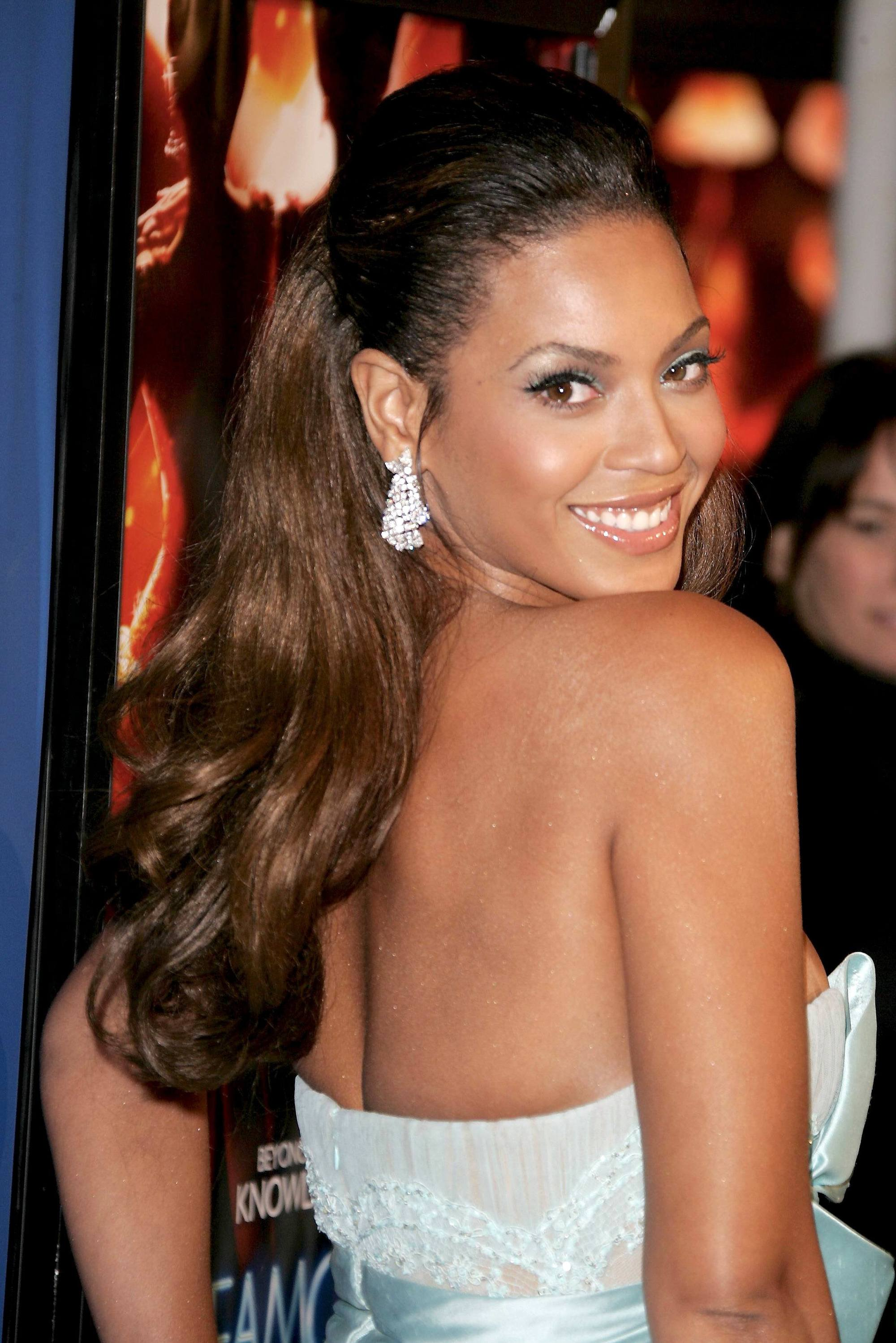 Side view of Beyonce with medium brown hair in half-up, half-down hairstyle with wavy ends
