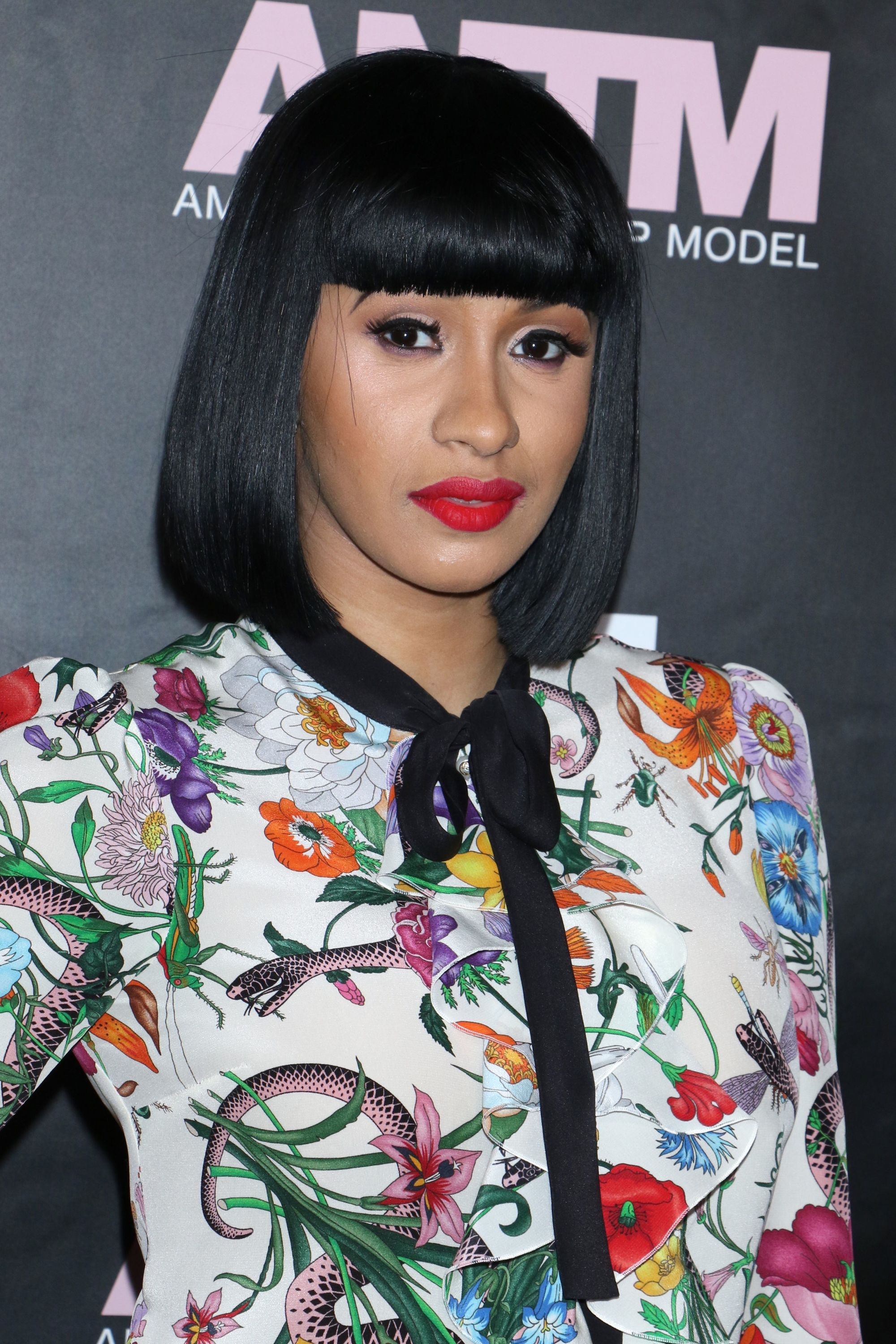 Cardi black bob with full bangs while wearing floral blouse