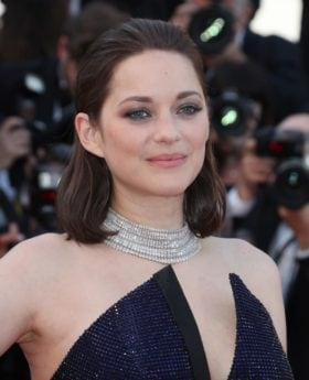 Marion Cotillard with long bob length dark brown hair smoothed back at red carpet premiere with strapless navy dress