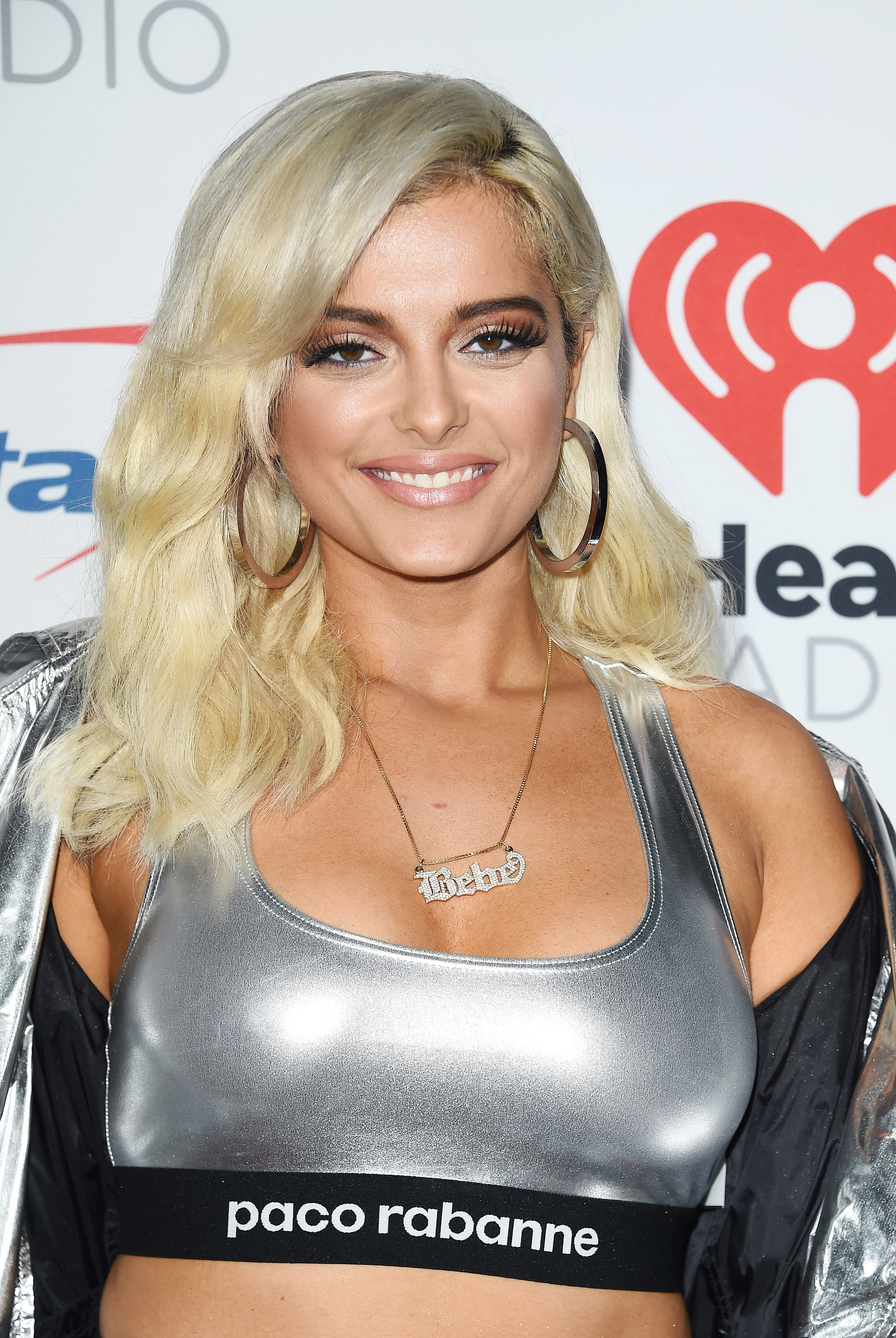 Bebe Rexha mid length platinum blonde hair in side parting with textured curls