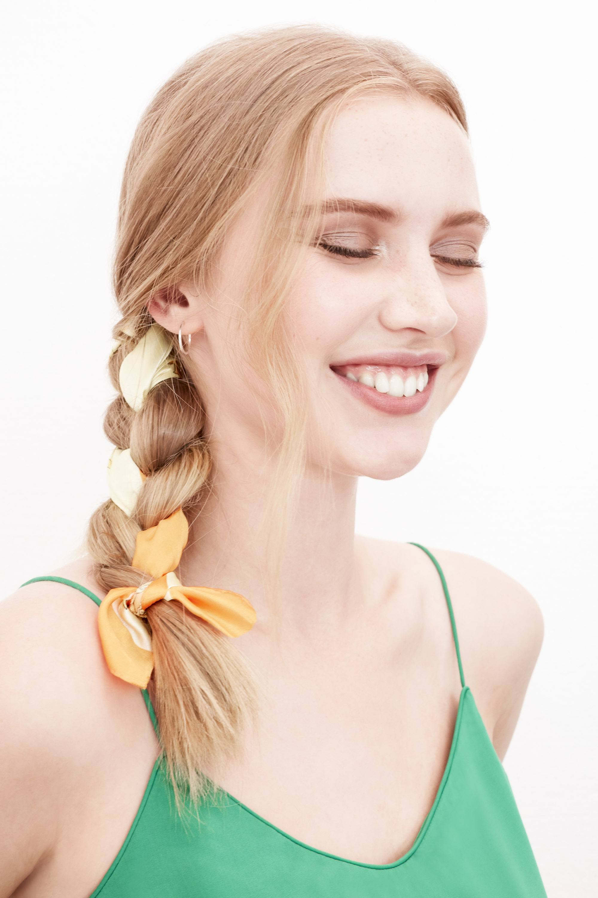 Easy braids for long hair: Photo of a blonde woman with a side braid with a yellow ribbon detail, wearing a green cami top